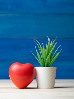 Red heart beside plant pot