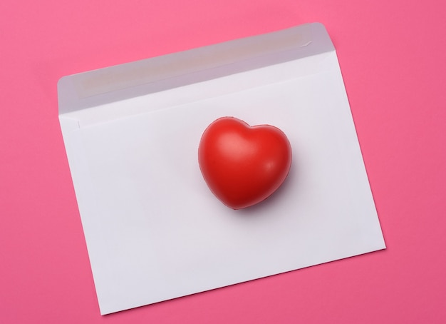 Red heart and blank white paper on a pink background, top view