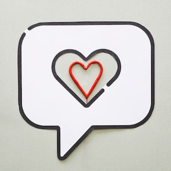 Red heart in bubble speech icon on table