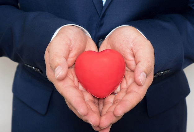 Red heart in businessman hand