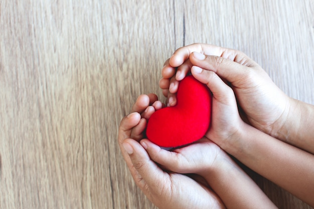 Red heart in child hands and parent hands on wooden table background with love and harmony
