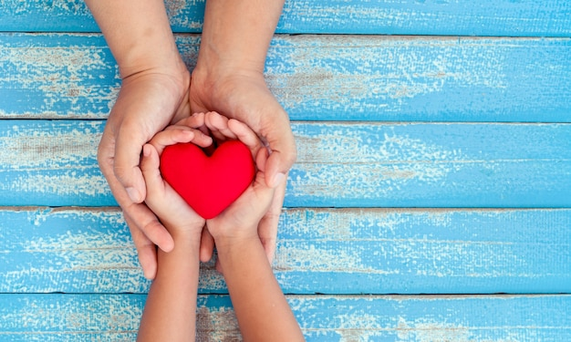 Red heart in child kid and mother hands on old blue wooden table