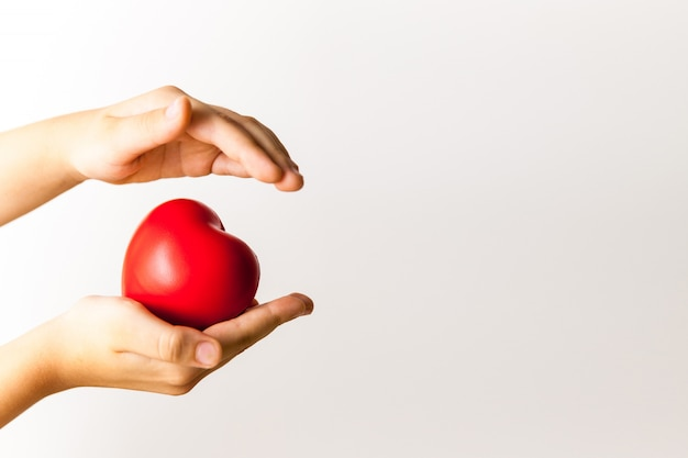 Red heart in child's hands on light background