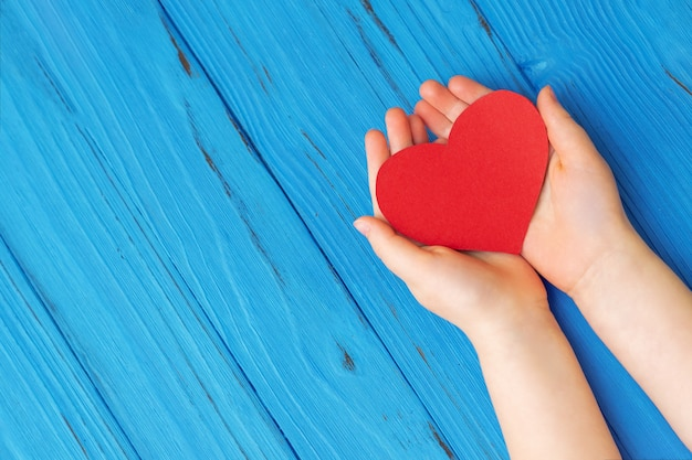 Red heart in child's hands