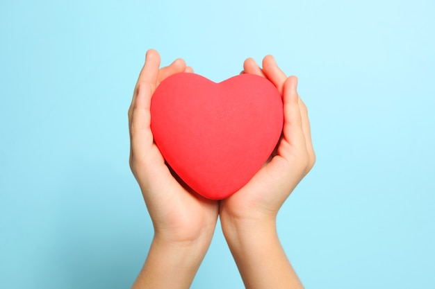 Red heart in childrens hands on a blue background close up