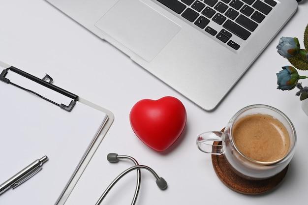 Красное сердце, буфер обмена и стетоскоп на рабочем месте врача. кардиология и концепция страхования.