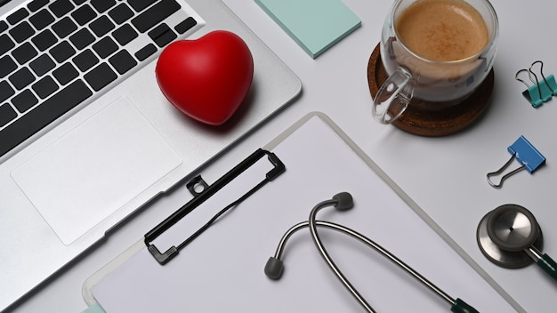 Красное сердце, буфер обмена, портативный компьютер и стетоскоп на белом фоне. концепция медицинского страхования.