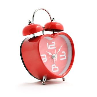 白い背景の上のベルと赤いハート時計