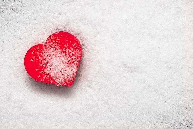 雪に覆われた赤いハート、愛、ロマンス、離婚、バレンタインデーについてのコンセプト写真。テキスト、レイアウト、上面図用のスペース