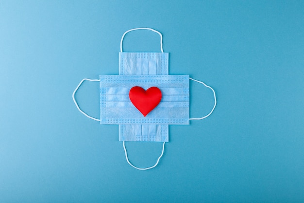Red heart and crossed anti-epidemic blue medical protective masks,