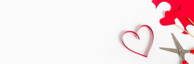 明るい白の背景に紙、はさみ、色の段ボールから切り取った赤いハート。作曲バレンタインデー。バナー。フラットレイ、上面図。