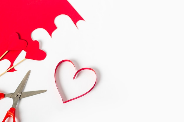 Red heart cut from paper, scissors and colored cardboard on a light white background. composition valentine's day. banner. flat lay, top view.