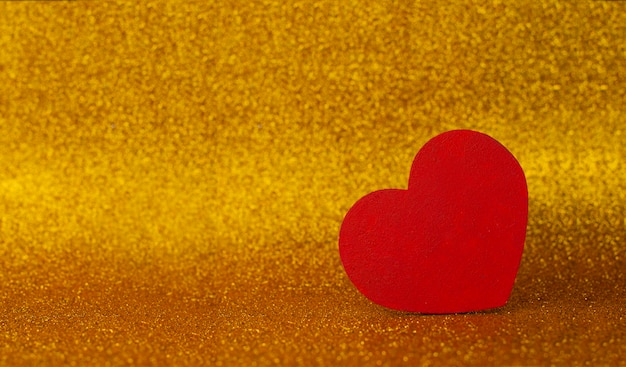 バレンタインデーのボケ味と光沢のあるゴールドの背景に赤いハートの装飾