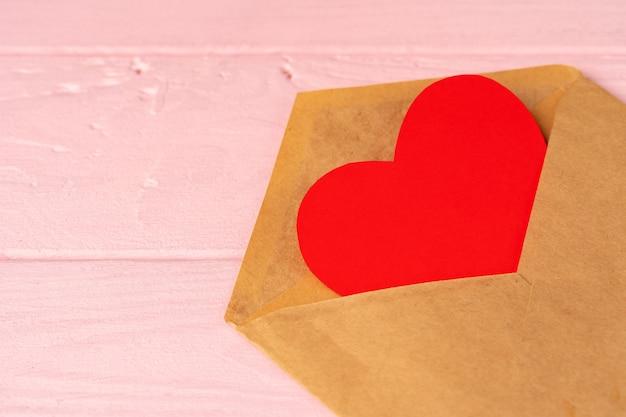 ピンクの木製テーブルの封筒に赤いハートの装飾