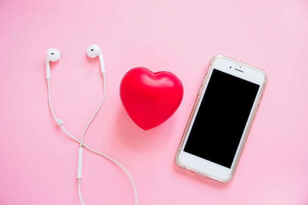 Red heart between the earphone and smartphone on pink background