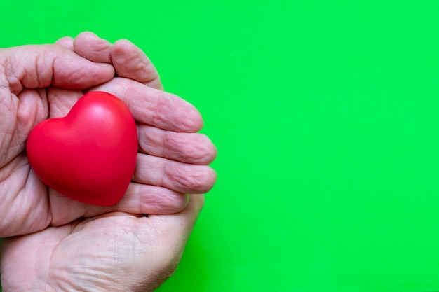 Red heart in elderly hands, with green background.