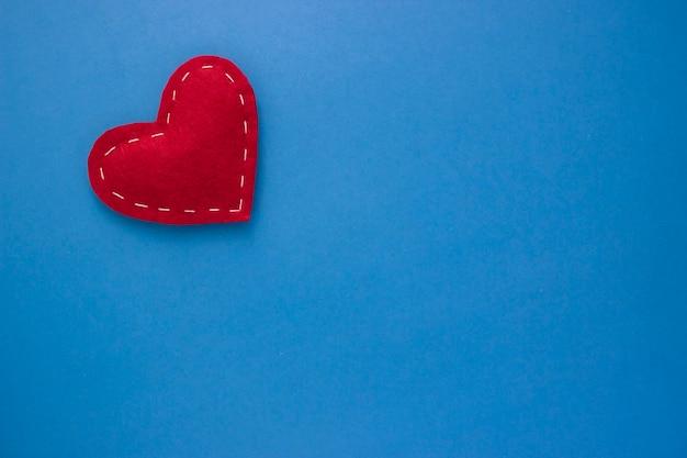 青い背景の上の白い糸と赤いハート生地愛、ロマンスのコンセプト。刺し繡のラインで明るい心を感じました。