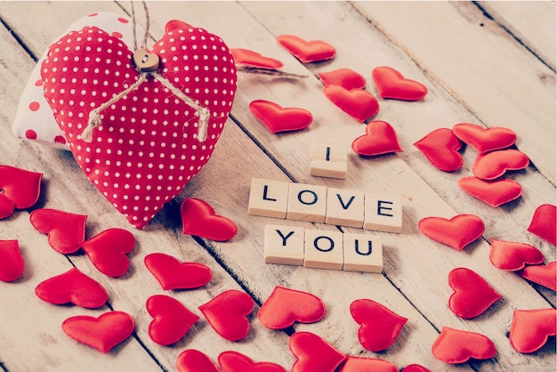Red heart fabric and wood text of i love you on wooden table background.