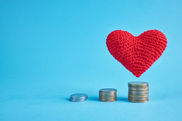 Red heart flying under coin stacks over blue. copy space. money coins stairs to love and romance concept. love to money concept