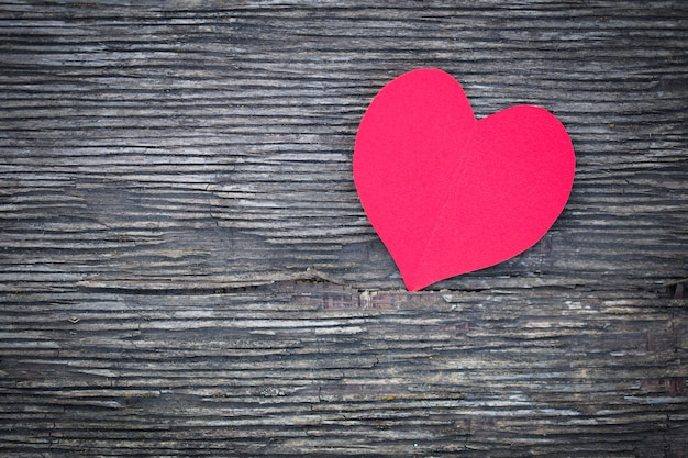 Red heart from a paper lies on an old board