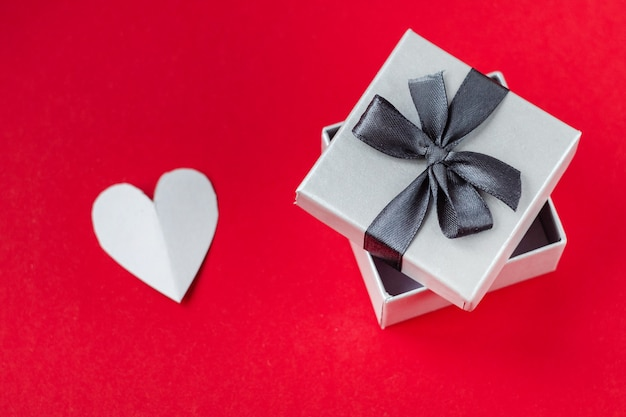 Red heart in gift box on red background