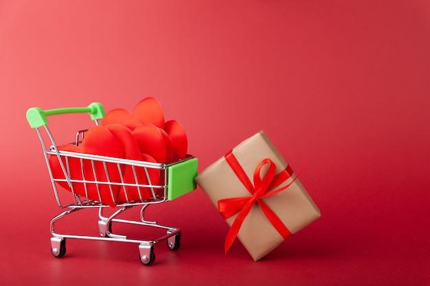 붉은 마음, 컬러 배경에 미니 식료품 카트 안에 빨간 리본이 달린 선물 상자