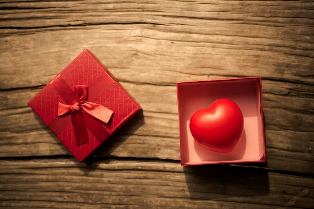Red heart in  gift box on wooden plank. concept for valentine day.