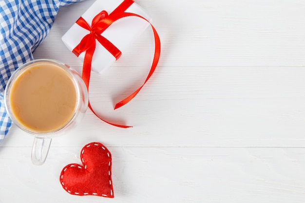 Red heart, gift, morning coffee against the of a white table, concept, a postcard for valentine's day.