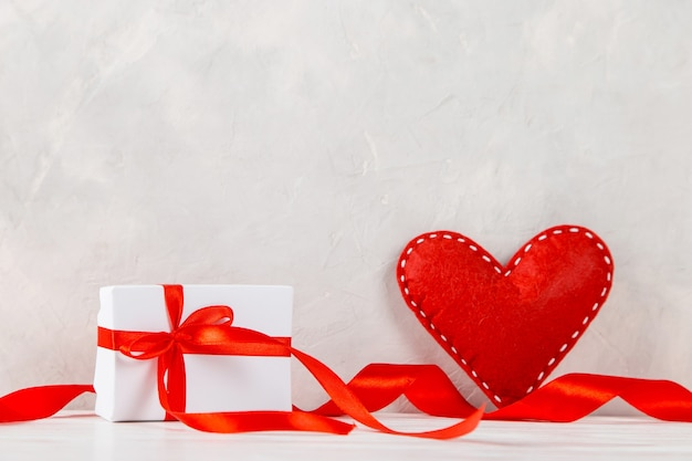 Red heart, gift, ribbon against the of a white wall, concept, a postcard for valentine's day.
