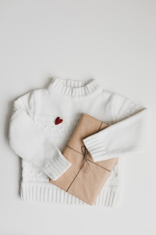 Red heart, a gift and a white knitted sweater. concept of preparing heart gifts. flat lay