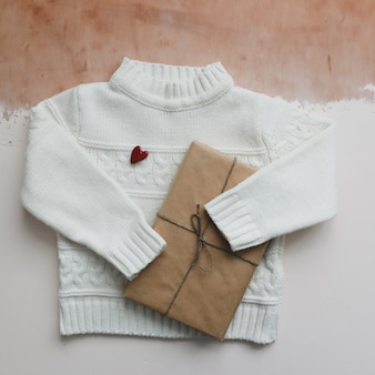 Red heart, a gift and a white knitted sweater. flat lay