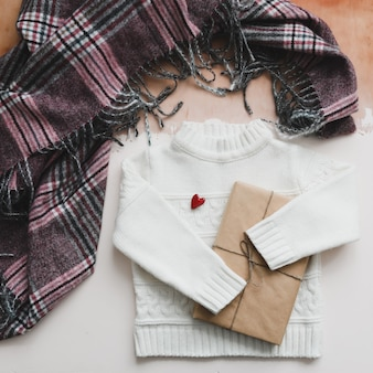 A red heart, gift and a white knitted sweater. top view, copy space