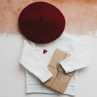 A red heart, gift and a white knitted sweater. top view