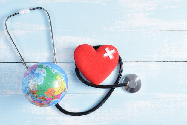 Red heart and globe on blue and white pastel wooden background. healthcare and medical concept.