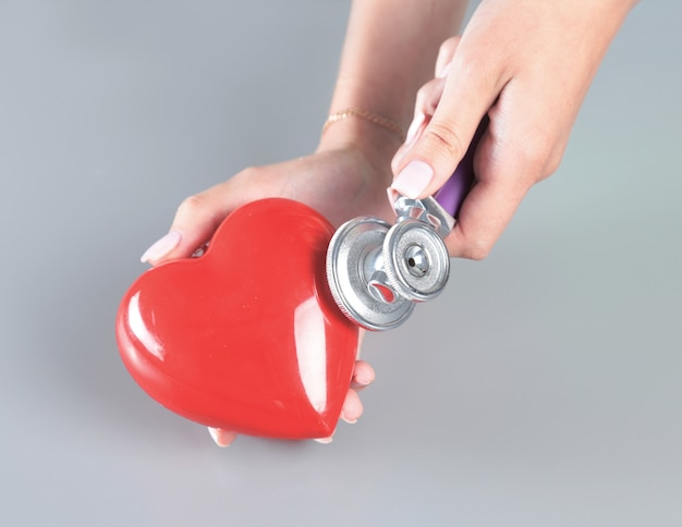 Red heart in hand's doctor with stethoscope