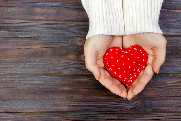 Red heart in hands closeup on wooden