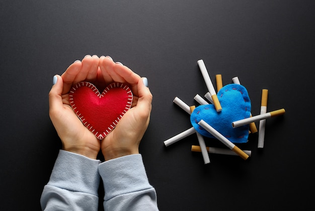 Red heart in hands nearby blue heart with cigarettes