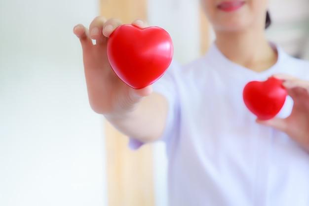 女性の看護婦の手を笑っている赤い心