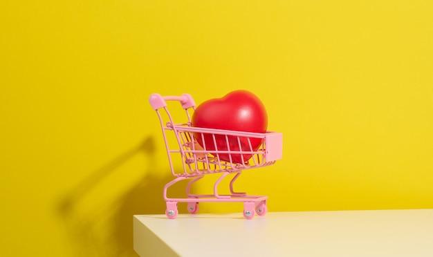 노란색 배경에 있는 상점에서 미니어처 금속 트롤리에 있는 붉은 심장. 장기 기증, 이식 개념