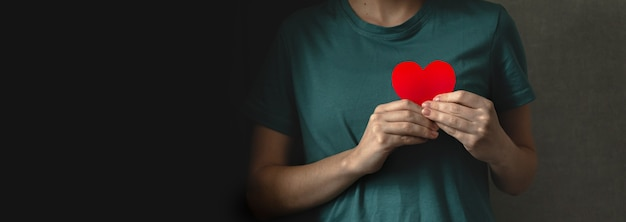 Красное сердце в руках. баннер с черным фоном. молодая дама дает свое фото концепции любви