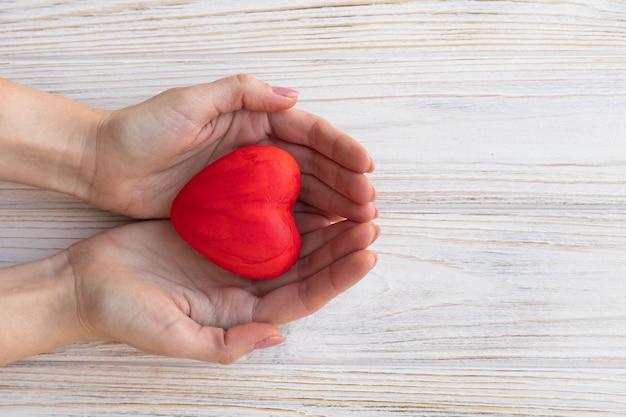 손에 붉은 마음, 심장 건강 개념, 평면도.