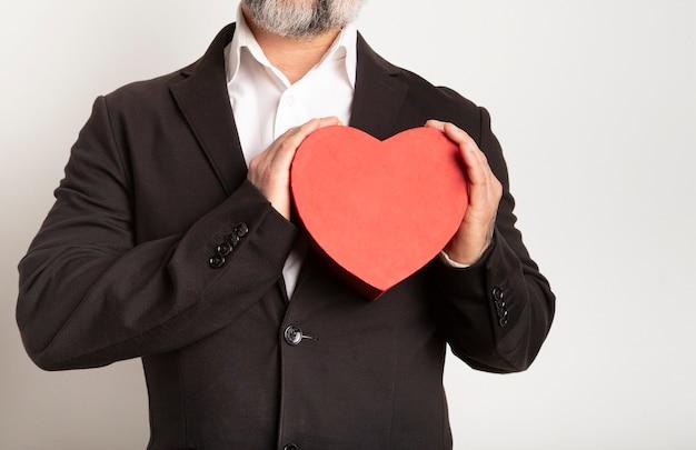 ハートジェスチャー、バレンタインの概念、白い背景の上のスーツの男と手に赤いハート