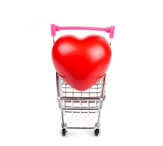 白い背景の上のショッピングカートの赤いハート血の圧力制御。ヘルスケアの概念