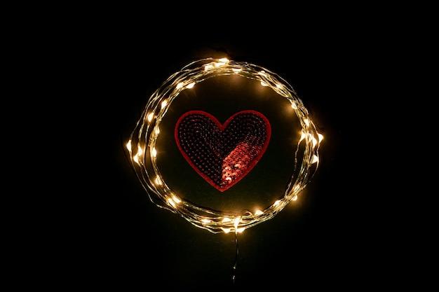 검은 배경에 휴일 축하 빛 갈 랜드의 원 안에 붉은 마음