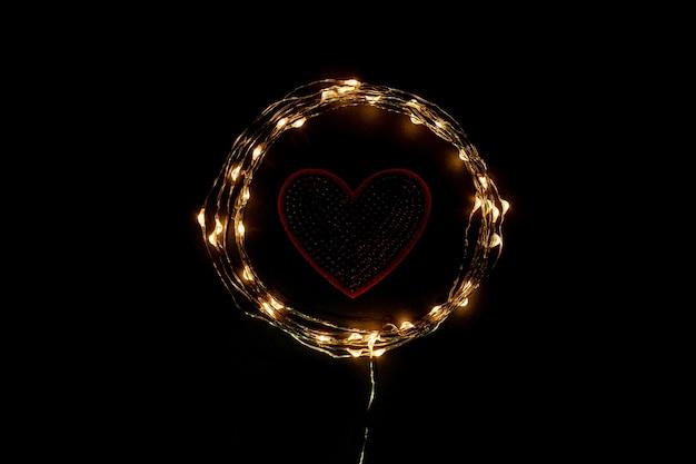 휴일 축 하 빛 갈 랜드의 원 안에 붉은 마음. 발렌타인 데이 개념