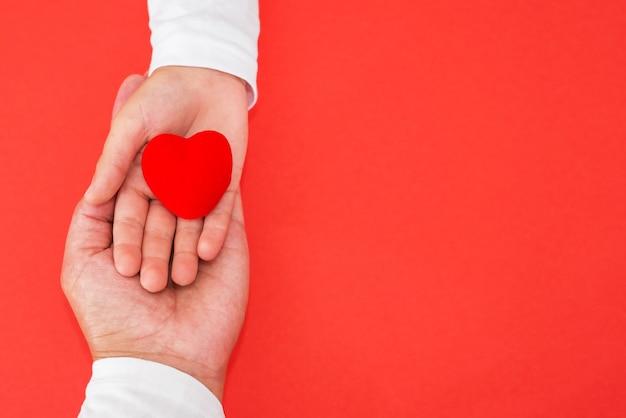 孤立した赤い背景の上の子供と母親の手に赤いハート。愛、憐れみ、同情の概念