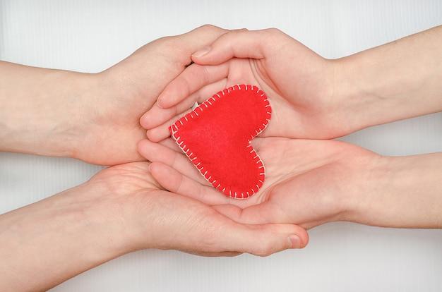 흰색 테이블에 남자와 여자의 사랑의 커플의 손에 붉은 마음. 발렌타인 데이, 가족, 사랑, 관계 만들기.