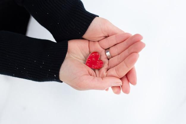 女性の手に赤いハート