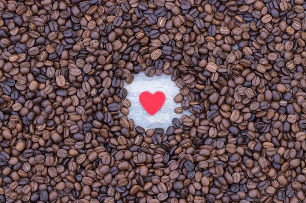 コーヒー豆の背景の真ん中に赤いハート
