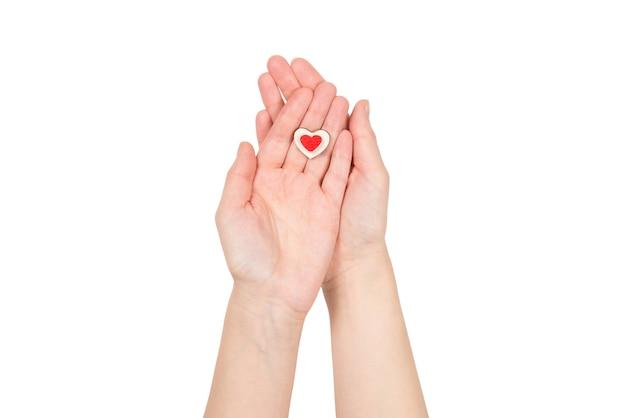 Красное сердце в изолированной руке женщины. скопируйте пространство.